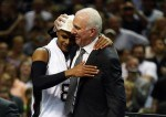 Gregg Popovich celebrates with Patty Mills #8 of the San Antonio Spurs