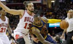 Cleveland Cavaliers' LeBron James (23) drives past Chicago Bulls Joakim Noah (13) during the third quarter of an NBA basketball game Sunday, April 5, 2015, in Cleveland. The Cavaliers defeated the Bulls 99-94.(AP Photo/Tony Dejak)