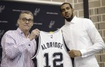 LaMarcus Aldridge, right, poses with San Antonio Spurs general manager R.C. Buford, left, and his new jersey during a news conference at the team's practice facility as he is formally introduced after he signed with the San Antonio Spurs NBA basketball team, Friday, July 10, 2015, in San Antonio. (AP Photo/Eric Gay)