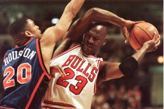 CHICAGO, IL - APRIL 18:  Chicago Bulls' guard Michael Jordan (23) keeps the ball away from New York Knicks' Allan Houston during the first half of their game at the United Center in Chicago 18 April.  (Photo credit should read DANIEL LIPPITT/AFP/Getty Images)