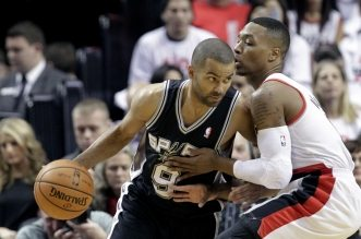 San Antonio Spurs guard Tony Parker, left, drives on Portland Trail Blazers guard Damian Lillard during the first half of an NBA basketball game in Portland, Ore., Saturday, Nov. 2, 2013. (AP Photo/Don Ryan)