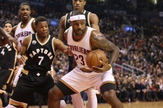 Nov 25, 2015; Toronto, Ontario, CAN; Cleveland Cavaliers forward LeBron James (23) comes away with a rebound against Toronto Raptors point guard Kyle Lowry (7) and guard DeMar DeRozan (10) at Air Canada Centre. The Raptors beat the Cavaliers 103-99. Mandatory Credit: Tom Szczerbowski-USA TODAY Sports